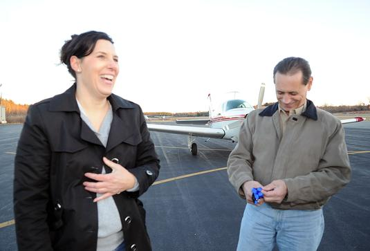 Michele Handley, left, and pilot Charles Melo talk after Malo flew Dasher to Taunton on Friday.