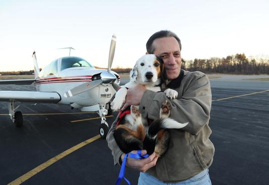 Pilot Charles Malo, 65, of Easton, who donates his time to Pilots N Paws, flew 8-month-old hound mix Dasher to Taunton on Friday.